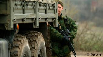 A Russian soldier standing behind a military vehicle