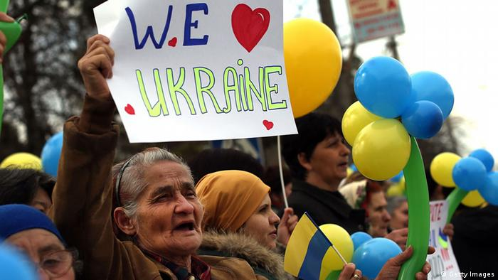 A woman at a demonstration in Bakhchysarai holds a sign reading I love Ukraine (Photo: Spencer Platt/Getty Images)