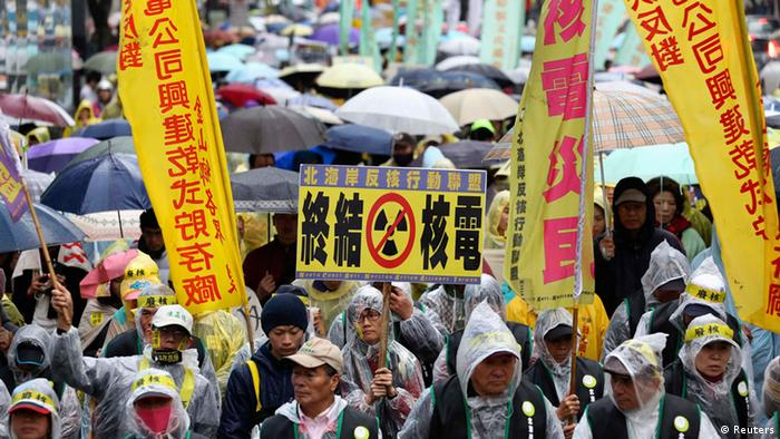 Demonstrators in raincoats and umbrellas march with banners and placards during an anti-nuclear protest on a street, amid rainfall in Taipei, March 8, 2014. REUTERS/Patrick Lin