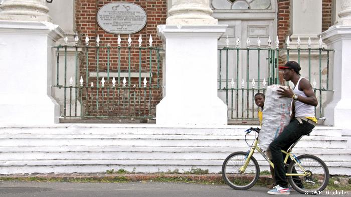A young man and a boy carry a large sack as they ride past the Old King's House on a bicycle