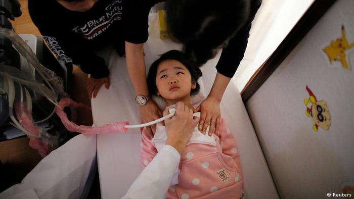 Menina asia´tica atendida por médicos em maca