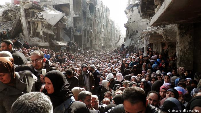 An undated handout picture made available on 26 February 2014 by the United Nation Relief and Works Agency (UNRWA) shows Palestinian and Syrian residents of Yarmuk Palestinian Refugee Camp crowding in a destroyed street as food is distributed, in Damascus, Syria. EPA/United Nation Relief and Works Agency /
