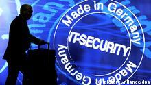 Ein Messebesucher geht am 08.03.2013 an einem Werbeplakat für IT-Security auf der weltweit größten Computermesse CeBIT in Hannover (Niedersachsen) vorbei. Foto: Peter Steffen