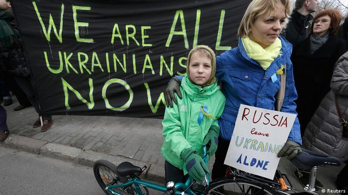 A woman and her daughter stand in front of a demonstration poster (Foto: Ints Kalnins/REUTERS)