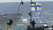 SEVASTOPOL, UKRAINE - MARCH 10: An armed sailor of the Ukrainian warship Ternipol stands on board under a Ukrainian naval flag as the ship lays anchored next to a Russian warship on March 10, 2014 in Sevastopol, Ukraine. Russian warships are standing nearby to prevent the Ternipol and the larger Slavutych from departing as a blockade by Russian-led forces of Ukrainian military facilities and assets continues on Crimea. The new pro-Russian Crimean government will seek to finalize secession for Crimea on March 16 and says any Ukrainian soldiers who have not surrendered or taken a pledge to the new Crimean state by then will face consequences. (Photo by Sean Gallup/Getty Images)