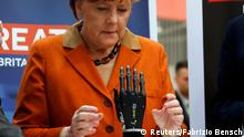 German Chancellor Angela Merkel looks at a bionic hand during a tour at the CeBIT technology fair in Hanover March 10, 2014. Britain is the partner country this year for the fair. REUTERS/Fabrizio Bensch (GERMANY - Tags: BUSINESS POLITICS SCIENCE TECHNOLOGY BUSINESS TELECOMS TPX IMAGES OF THE DAY) German Chancellor Merkel looks at a bionic hand during a tour at the CeBIT technology fair in Hanover