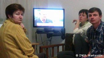 Two women and a man sit in front of the TV (Foto: Alexander Warkentin/DW)