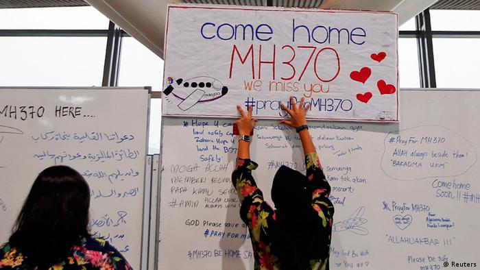 A woman places a sign of support and hope for the passengers of the missing Malaysia Airlines flight MH370 that she made and brought to the Kuala Lumpur International Airport (Photo: Reuters)