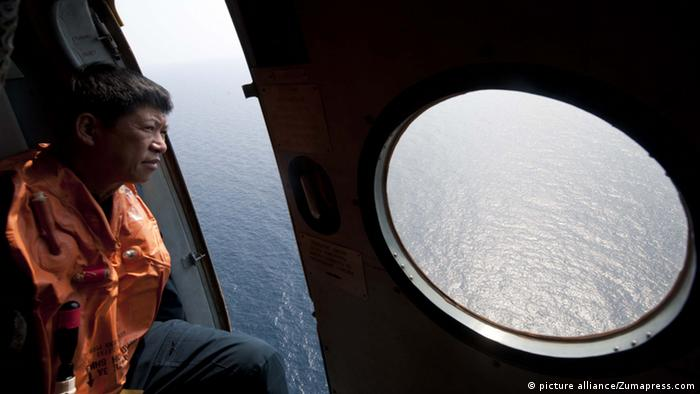 A searcher looks out of a plane window over the ocean in the hunt for flight MH370