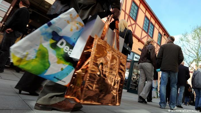 Mit vielen Einkaufstaschen in der Hand geht ein Kunde am durch das Designer-Outlet in Neumünster (Schleswig-Holstein). (Foto: Carsten Rehder, dpa)