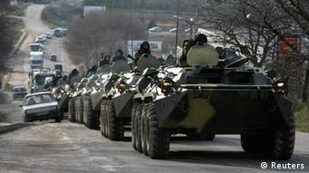 Soldiers, believed to be Russian, ride on military armoured personnel carriers on a road near the Crimean port city of Sevastopol Photo: REUTERS/Baz Ratner (