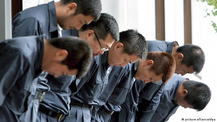 Yamaguchi-gumi members bow as leaders of the criminal organisation leave its headquarters in Kobe, Western Japan, Wednesday 05 October 2005.