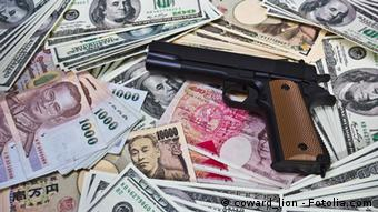 A gun placed on iternational currencies portrays linkage of international crime.