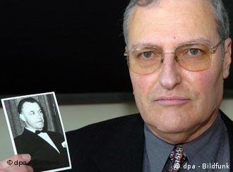 Efraim Zuroff, head of the Simon Wiesenthal Center holds up a photo of Heim