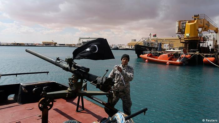 Libyan federalist militants stand on a boat with a large machine gun on it.