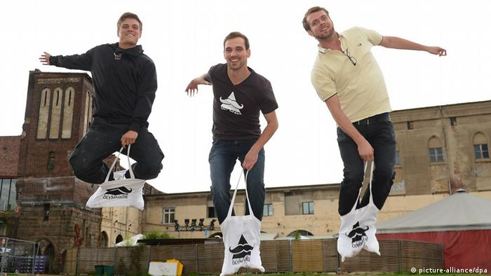 Group of three young men jumping in bags up in the air, like they're racing Photo: Britta Pedersen dpa/lbn