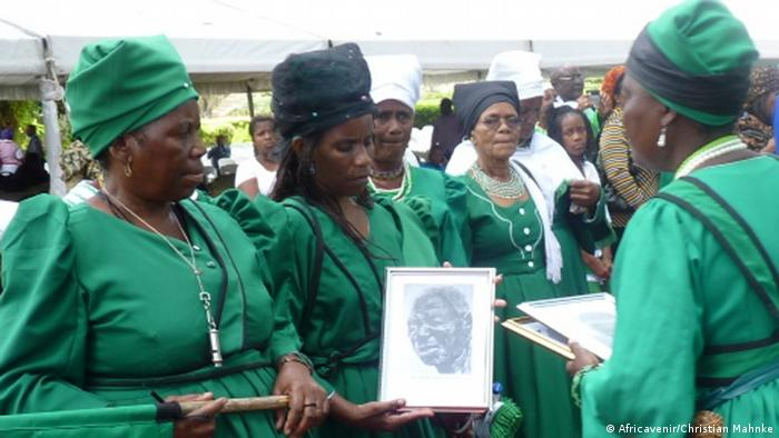 Herero women hold up a picture and remember the victims of the genocide