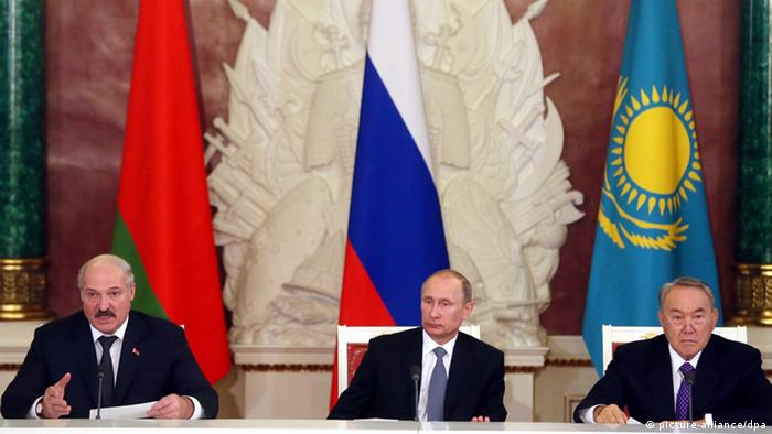 Presidents of Russia, Belarus and Kazakhstan seated in front of national flags.