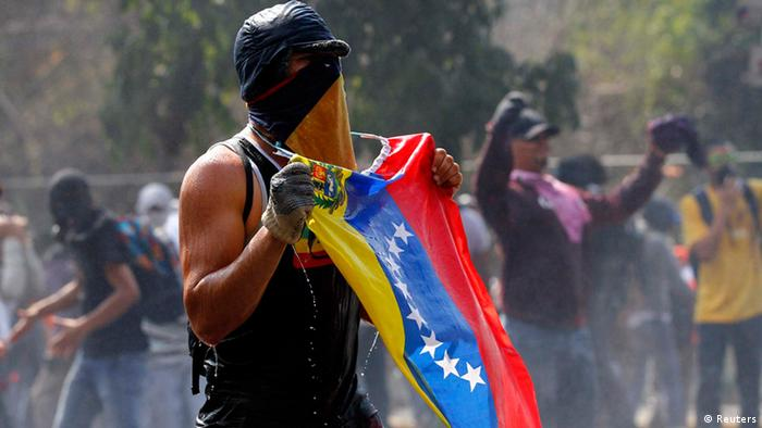 A protesters with his face covered holds a Venezuelan flag (Foto: Carlos Garcia Rawlins/REUTERS)