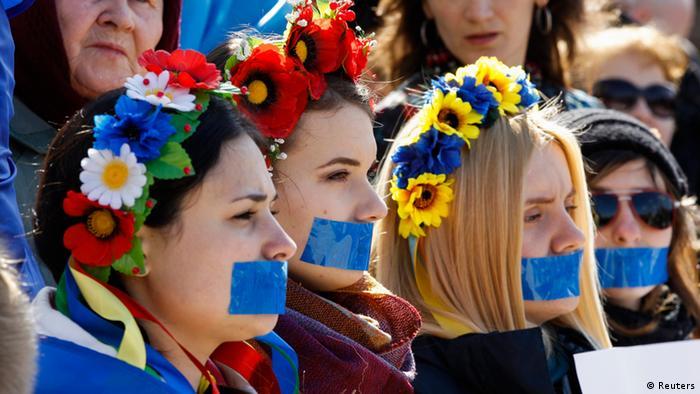 Mit traditionell ukrainischem Blumenschmuck im Haar und zugeklebtem Mund begeben sich diese jungen Frauen in den Widerstand. (Foto: Reuters)