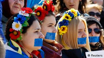 Women with flowers in their hair in a traditional Ukrainian style and blue tape over their mouths at a pro-Ukraine rally Photo: REUTERS/Vasily Fedosenko