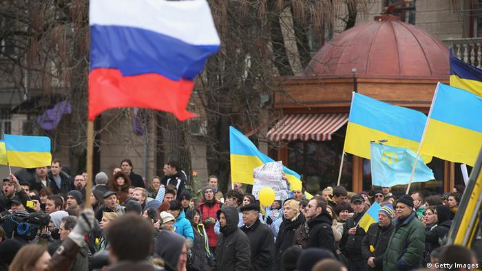 Pro-Russian sympathizers bearing a Russian flag march past pro-Ukrainian sympathizers gathered and waving Ukrainian flags as Russia's invasion of Crimea took place in Simferopol, Crimea in March of 2014