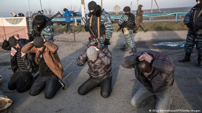 Pro-russische Sicherheitskräfte durchsuchen Männer am Checkpoint von Tschongar. (Foto: AFP)