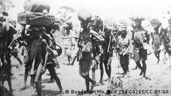 A group of soldiers and bearers on the march