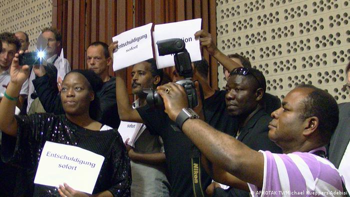 People holding up a posters that read 'Apology now'