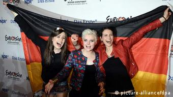 The three members of Elaiza, holding a German flag