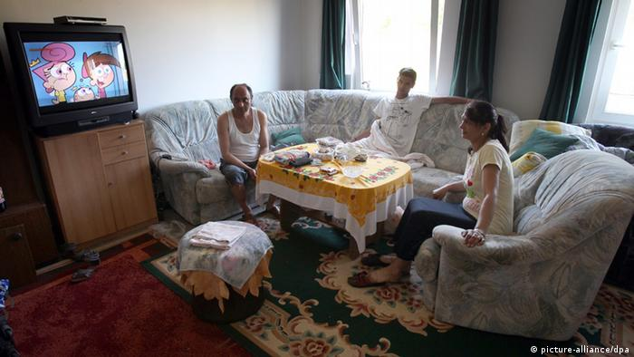 A Serbian family sits on a couch, watching TV