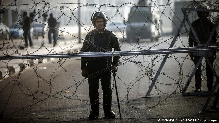 Policeman stands guard outside the police academy (Mahmoud Khaled/AFP)
