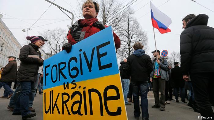 Участница протестной акции в Москве в марте 2014 года с плакатом в виде украинского флага и надписи на английском Прости нас, Украина