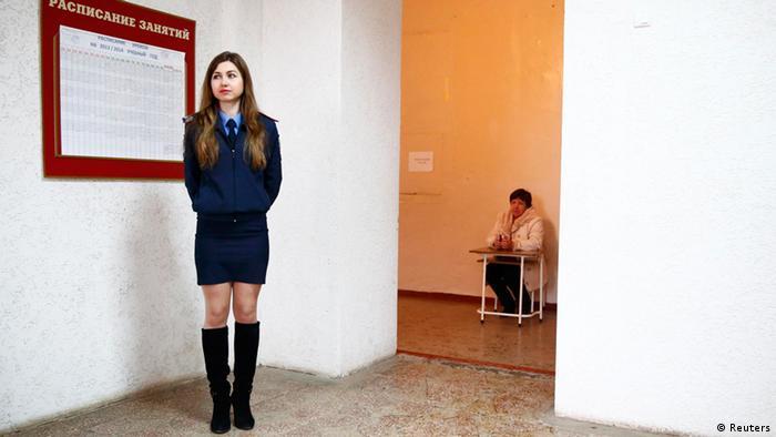 Eine junge Polizistin bewacht ein Wahllokal in Simferopol. (Fotos: Reuters)