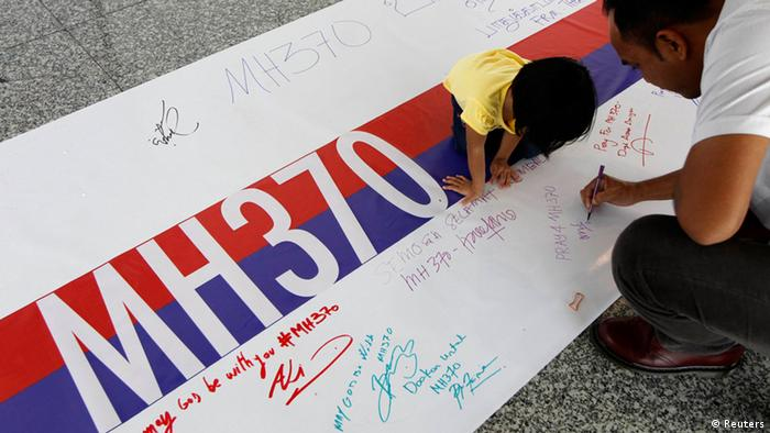 A man signs a poster with MH370 written on it (Foto: Edgar Su/REUTERS)