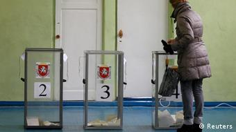 A woman casts her ballot during the referendum on the status of Ukraine's Crimea region at a polling station in Simferopol March 16, 2014.