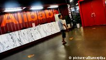 --FILE--A man walks past the reception desk at the headquarters of Alibaba Group in Hangzhou city, east Chinas Zhejiang province, 20 August 2013. Chinese e-commerce giant Alibaba Group Holding is 95 percent certain to choose New York as the venue for its initial public offering, according to media reports, citing unnamed sources close to the deal. The company is no longer discussing a potential listing in Hong Kong. The companys listing venue has been up in the air since last year, after Hong Kong regulators refused to bend on their one share-one vote stance. Alibaba has planned an IPO with a shareholder structure that allows a group of top managers and founders to nominate and control the board, while holding only around 13 percent of the companys shares.