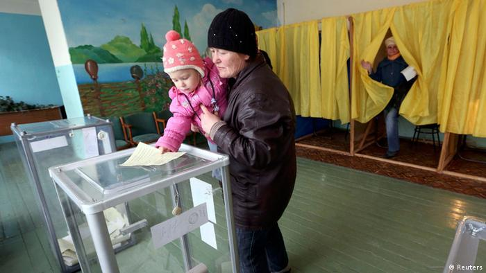 Referendum in Crimea, March 16, 2014. Woman holding a young child in her5 arm casts her vote in a ballot box