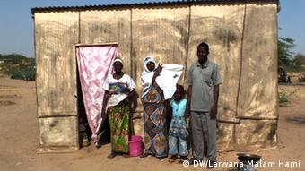 A refugee family from Nigeria stands outside an emergency shelter.