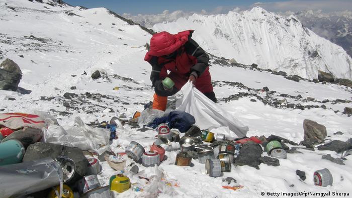 A climber picks up trash on Mount Everest