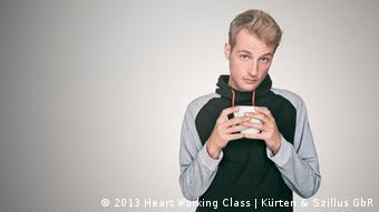 Ein Porträt zeigt den blonden Weekend aka Christoph Wiegand mit schwarzer Weste und einer Kaffetassse in der Hand in nachdenklicher Pose. (Foto: carlofeick,2013; Heart Working Class)