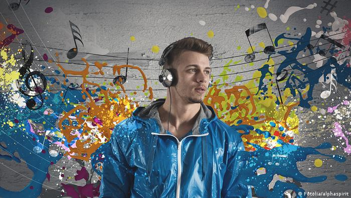 A young man listens to music against a colorful backdrop