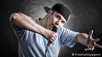 Rapper mit schwarzer Kappe und hellblauem T-Shirt spricht ins Mikro und untermauert sein Statement mit Gestik und Mimik. (Foto: Fotolia)