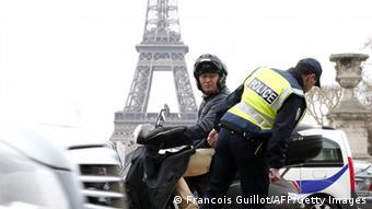 Полицейский проверяет багажник у мотоциклиста на фоне Эйфелевой башни