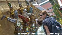 Foreign tourists look at sculptures as they visit at the Grand Palace in Bangkok on March 18, 2014. Thailand announced the end of a nearly two-month-old state of emergency in Bangkok and surrounding areas, hoping to lure back foreign visitors following an easing of deadly political protests. AFP PHOTO/PORNCHAI KITTIWONGSAKUL (Photo credit should read PORNCHAI KITTIWONGSAKUL/AFP/Getty Images)
