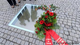 Para não esquecer: uma placa de vidro cobrindo um buraco no chão; dentro, prateleiras vazias