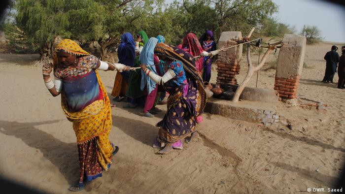 Thari women pull the rope to pour water from a well in the drought-hit area of the vast desert (Photo: Raffat Saeed/DW)