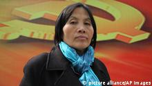 In this March 23, 2013 photo and released by Pablo Diez, human rights activist Cao Shunli, poses for photos next to a Communist Party propaganda banner in Beijing. Chinese authorities Monday, March 17, 2014 denied the accusation that the death of a human rights activist was due to the denying of her medical attention from security agents. Cao Shunli, 52-year-old activist who was arrested last year after staging a sit-in at China¿s ministry of foreign ministry asking for the authorities to allow the public to participate in a national human rights review, died on March 14, 2014 in a hospital in Beijing. (AP Photo) SPAIN OUT p