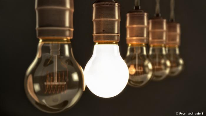 Fünf Glühbirnen in einer Reihe, von denen eine leuchtet