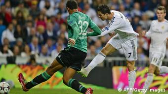 Real Madrid's Portuguese forward Cristiano Ronaldo (R) scores in front of Schalke's Cameroonian defender Joel Matip during the UEFA Champions League round of 16 second leg football match Real Madrid vs Schalke 04 at the Santiago Bernabeu stadium in Madrid on March 18, 2014. AFP PHOTO / JAVIER SORIANO